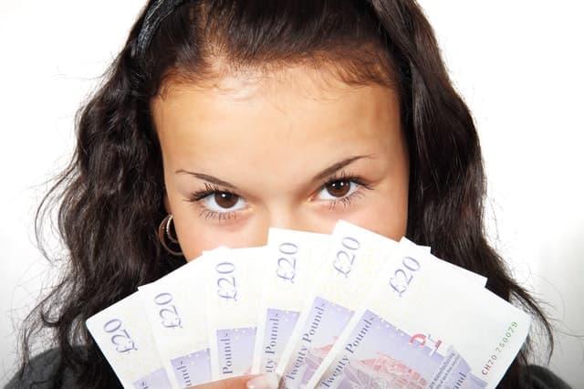 20ポンド紙幣を見せびらかす女性の画像