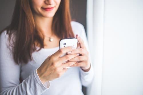 スマホを持つ女性の画像