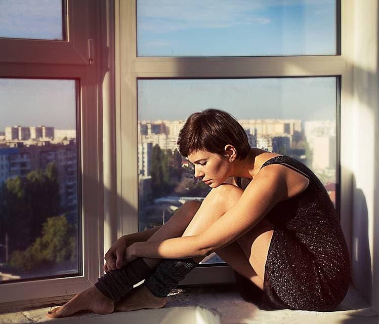 太陽の光を浴びながらベンチに座る女性の画像