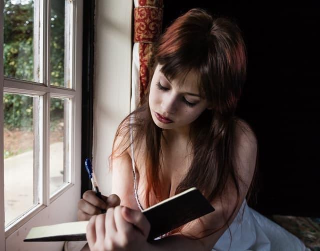 ペンを片手に窓辺で本を開いている女性の画像
