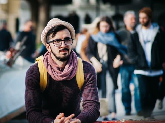 不機嫌そうに座っている帽子をかぶった男性のサムネイル画像