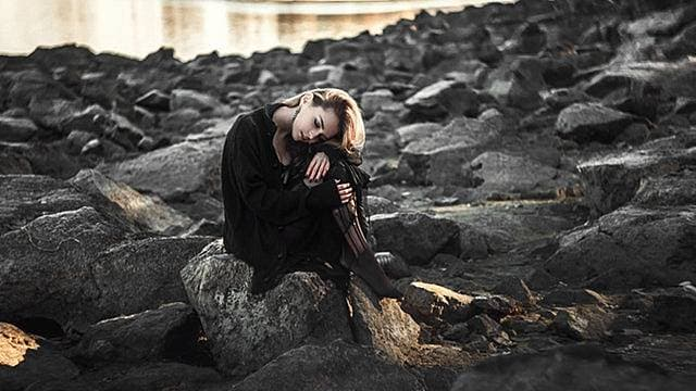 岩場で膝を抱え孤独に満ち足りている女性の画像