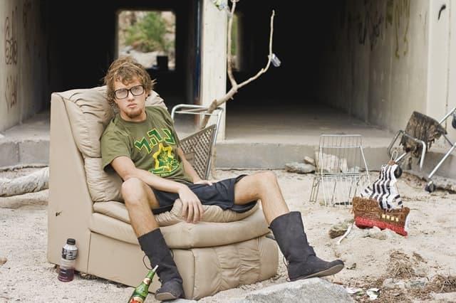 廃墟めいた砂場でソファーに腰掛ける外国人男性のサムネイル画像