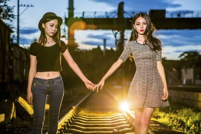 線路の上を手をつないで歩んでいく2人の女性のサムネイル画像