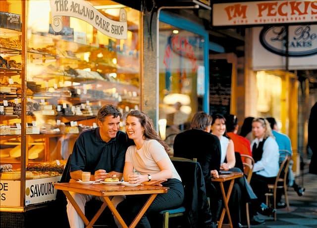 ケーキ屋さんのテラス席でほほえむ外国人カップルのサムネイル画像
