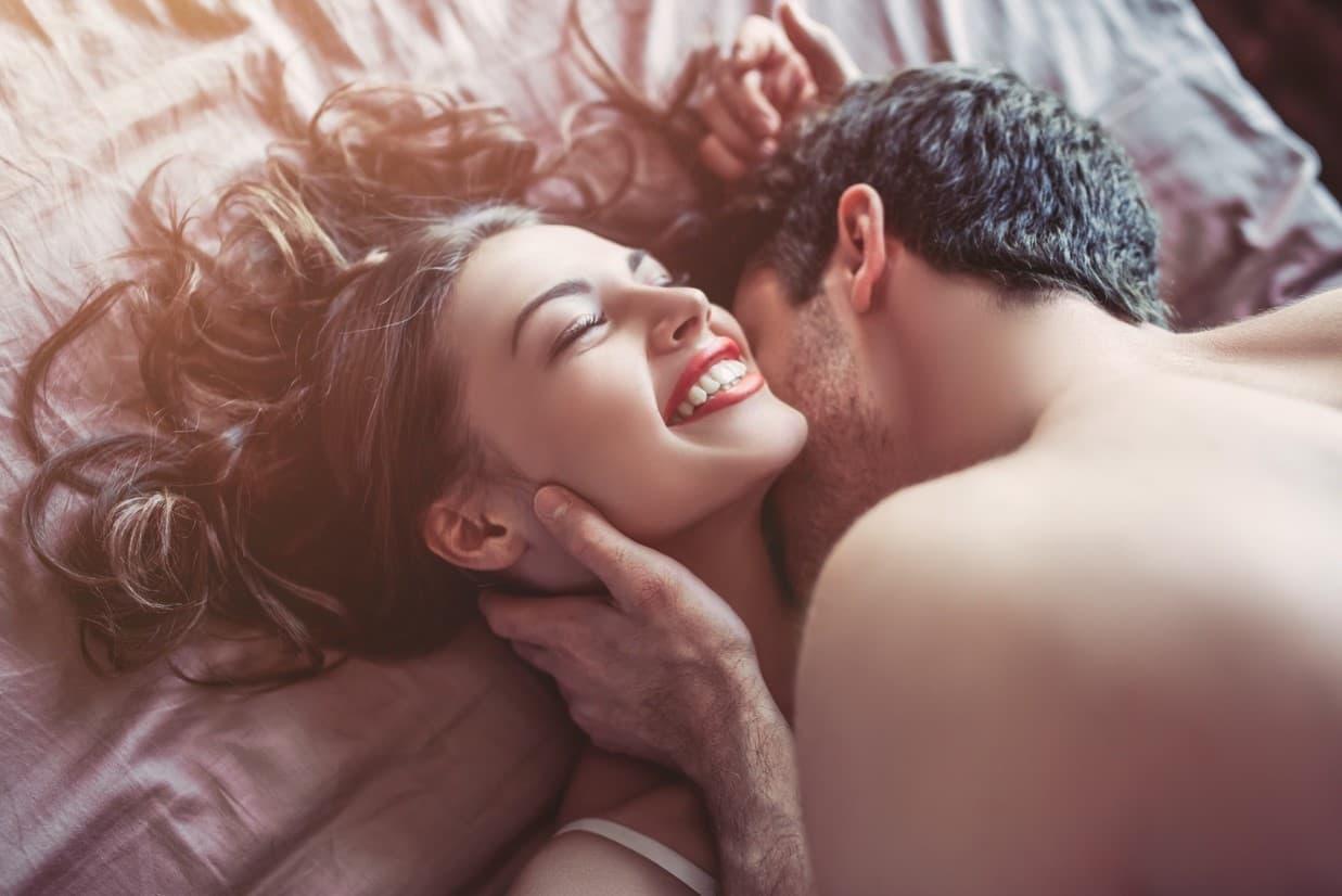 ベッドのなかで首筋にキスされた微笑む外国人女性の画像