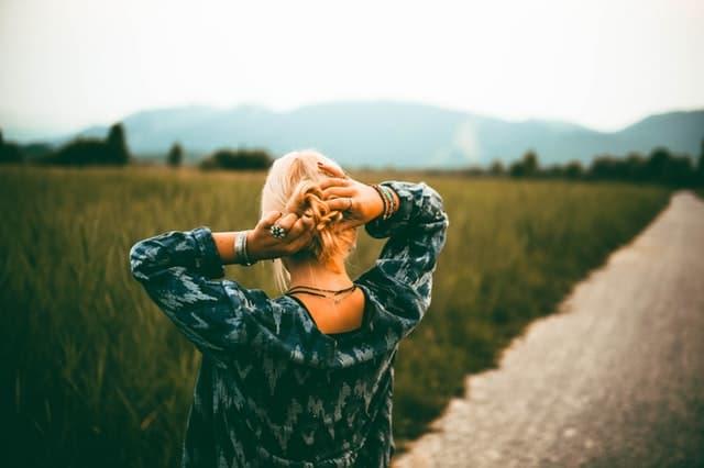 髪を結びながらどこまでも伸びていく道を眺める女性のサムネイル画像