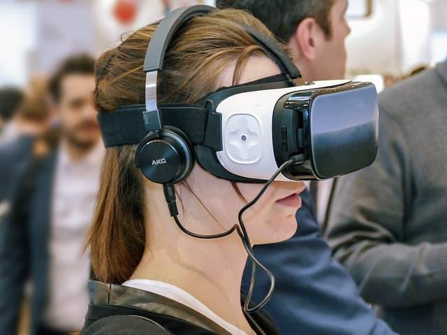 ヘッドマウントディスプレイを装着してVRを体験する女性のサムネイル画像