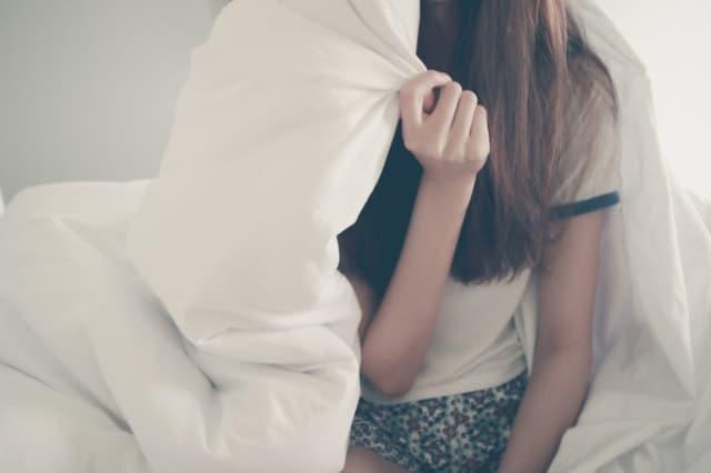 部屋着で分厚い布団にくるまる女性のサムネイル画像