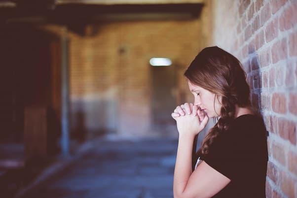 レンガの壁に背中を預けて手を組み祈る三つ編の女の子の画像