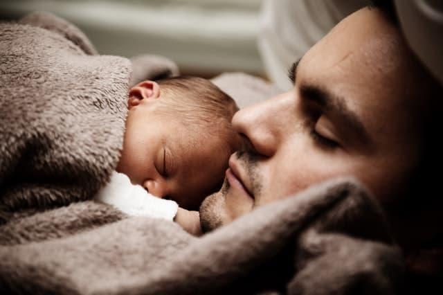 乳幼児を胸に抱いたまま毛布で眠る男性の画像
