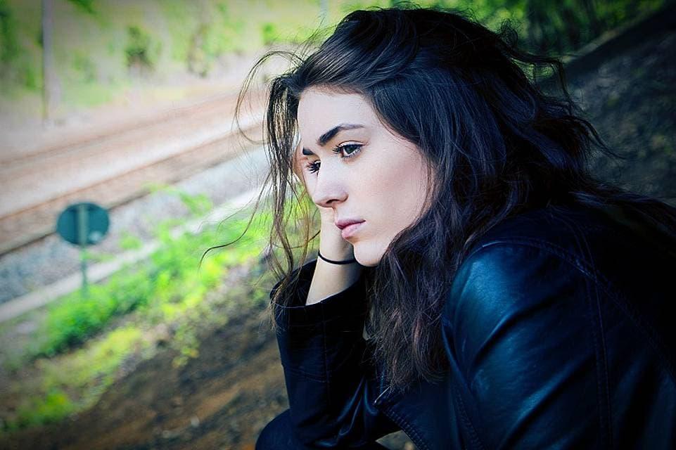 何かを待つようにして頬杖をつきひとり考える女性の写真
