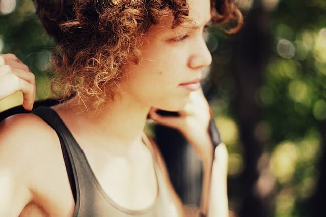 ブランコに乗る巻き毛の少女の横顔の画像