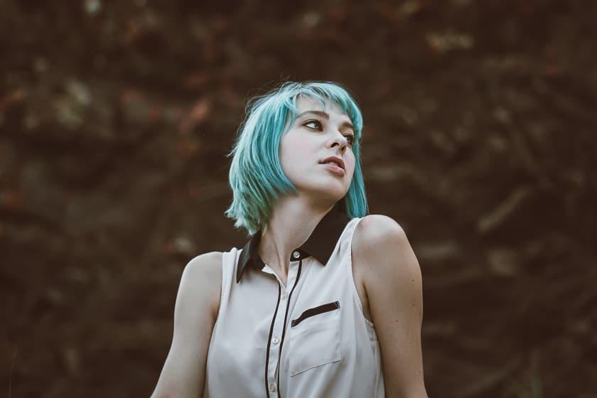 ノースリーブを着た遠くを見つめる青緑色の髪の女性
