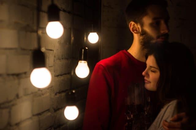 温かい光のもとで抱き合うカップルの画像