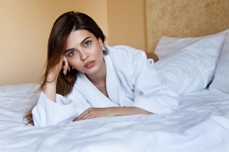 バスローブを着た青い目の女性がベッドの上で横になっている画像