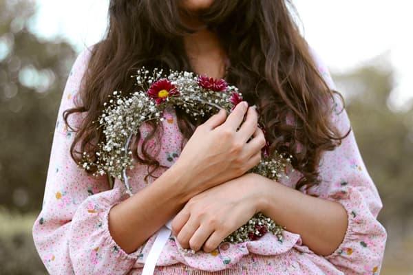 胸元で花冠を抱えもつ少女の画像