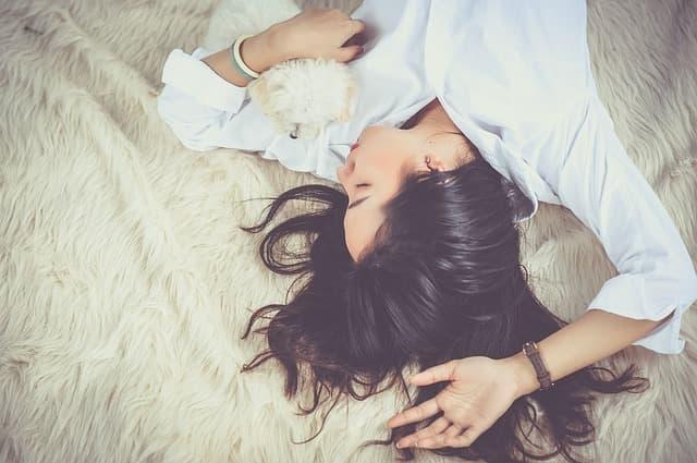 毛の長い絨毯の上で白いシャツの女性が仰向けに寝ている画像