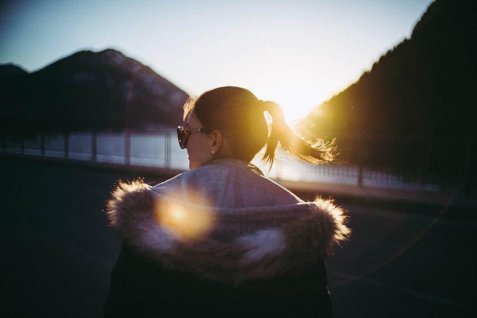 光の射す方へ向かって歩く女性の写真