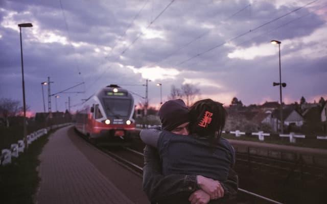 次の列車が来ているホームで抱き合う男女のカップルの画像