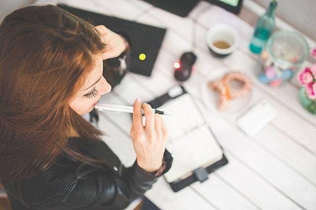 ペンを持ちながらデスクで考え事をしている女性の写真