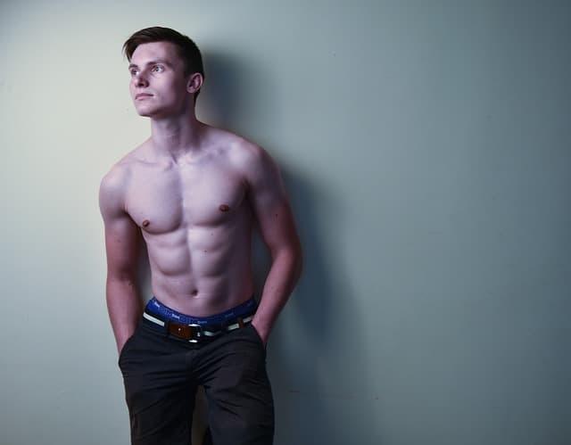 白い壁の前でポケットに手に入れたまま視線を外す上半身裸の筋肉質な男性の画像