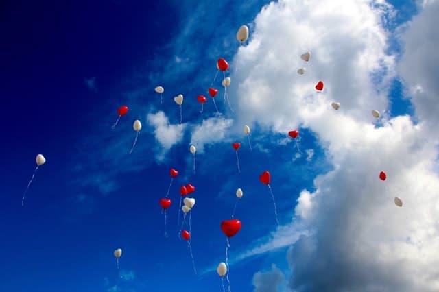 群れのように空へと飛んでゆくハート型の赤と白の風船の画像