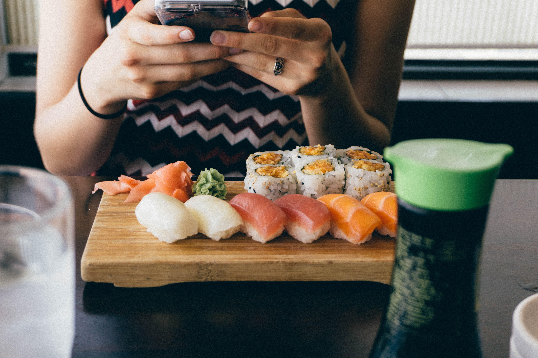 女性がにぎり寿司を写真に撮っている画像