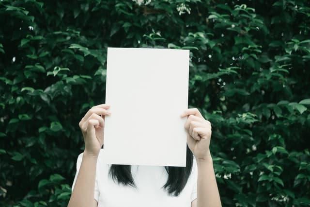 自分の顔の前に真っ白な紙を掲げる女性の画像