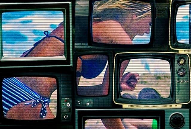 いくつものブラウン管テレビに水着の女性が映っている画像