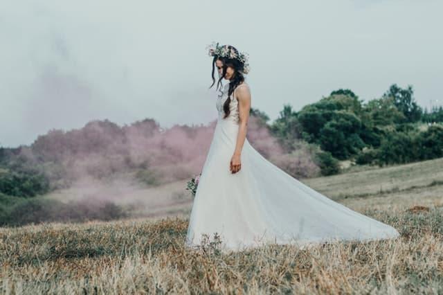 枯れ草の上をひとり寂しく歩くウェディングドレス姿の女性の画像