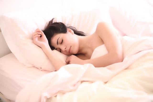 ふかふかの真っ白なベッドと枕で寝ている裸の女性の画像