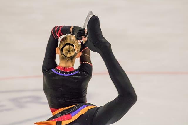 黒い衣装を着た女子フィギュアスケート選手の後姿の画像