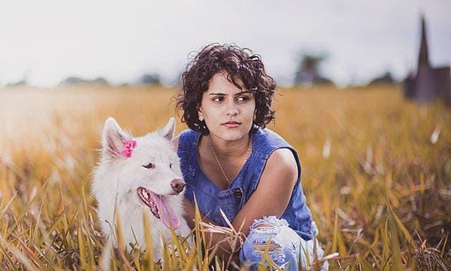 女性が犬と一緒にたたずんで座り込む画像