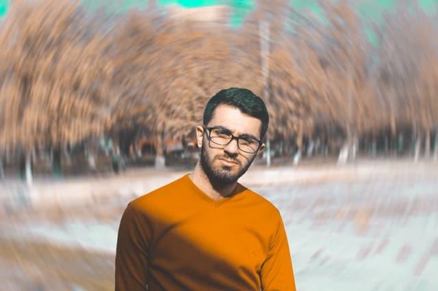 オレンジ色の服を着た男性と渦巻く秋の風景の画像