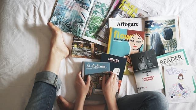 ベッドの上に雑誌や本を何冊も並べて読んでいる画像
