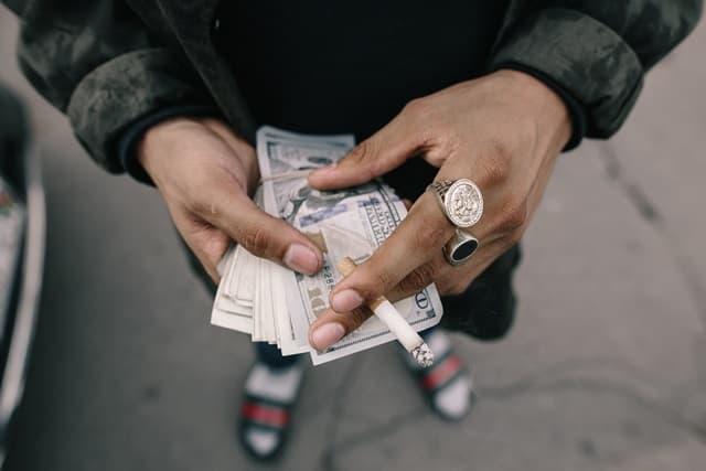ごつい指輪をつけた男性がたばこを持ちながら紙幣を数えている画像