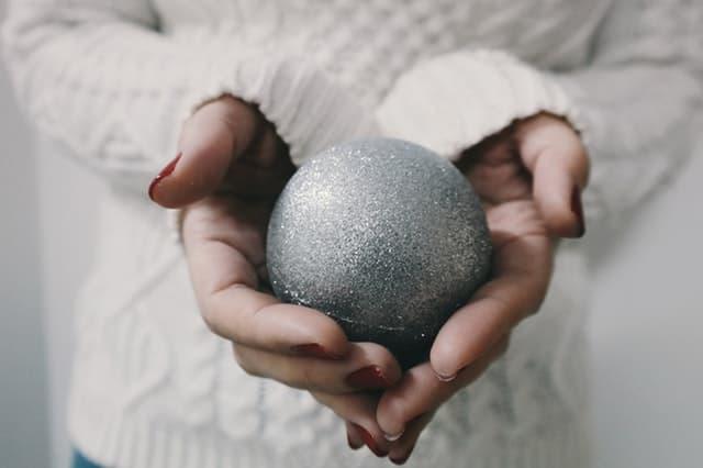 白いニットを着た女性が赤いマニキュアを塗った手で銀色の玉を大事に包み込む画像