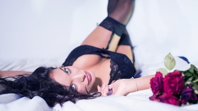 バラの花束とともに白いシーツの上に寝転ぶ、黒いガーターベルトと黒いブラジャーを着けた女性の画像