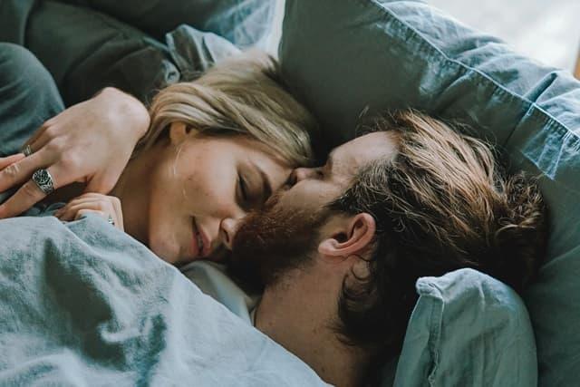 男性から額にキスされながら眠る女性の画像