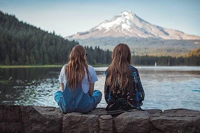 山を望む湖のほとりで座る2人の金髪の女性の後姿の画像