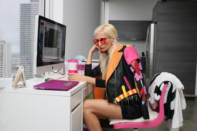 黒とオレンジとピンクのレザージャケットを羽織った女性の画像