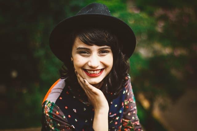 黒いハットを被った満面の笑みの女性の画像