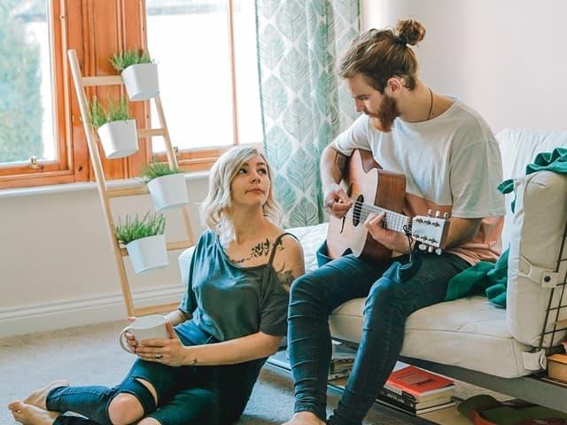 髭をたくわえた男性がギターを弾いている姿を床に座って聴いている女性の画像