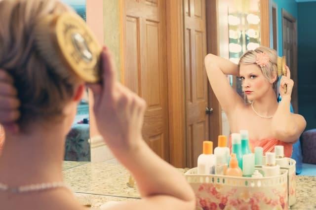 鏡で自分の顔を見つめる女性