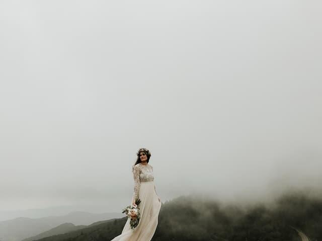 殺風景な霧の山でひとり寂しげにたたずむ新婦の画像