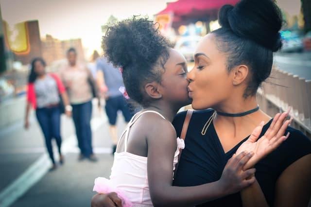 頬に口づけしあう黒人母娘の画像