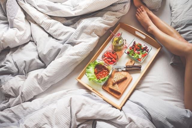 サラダとホットサンドの乗ったプレートとベッドで寝転ぶ女性の脚の画像
