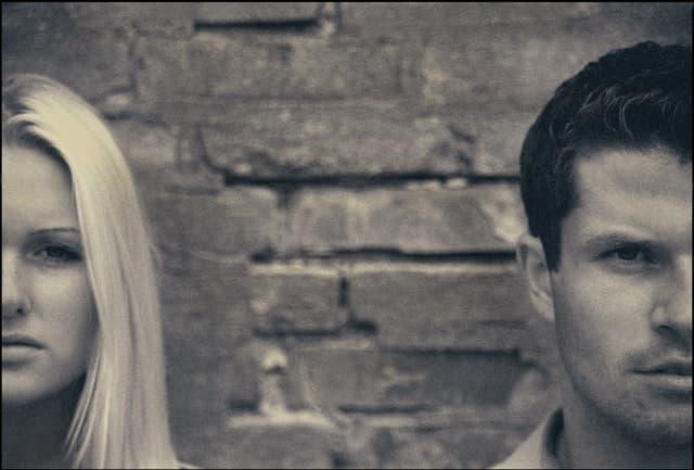無表情で並ぶ男女2人のモノクロ画像