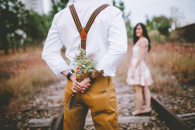 線路の上で後ろ手に花束を隠しながら女性に話しかけるサスペンダー姿の男性の画像